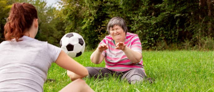 Woman and her carer playing football in the park