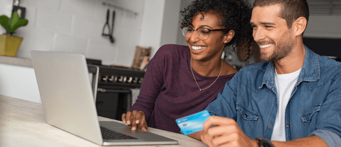 Couple sit in home making an online payment