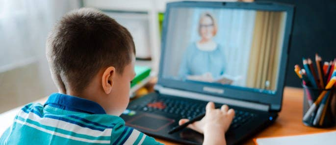 Young boy working with his tutor in a virtual classroom