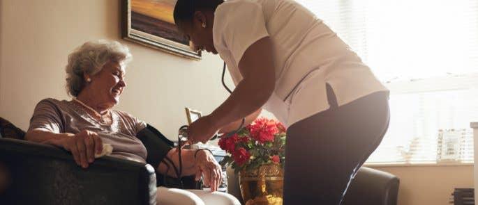 Nurse checking lady's blood pressure