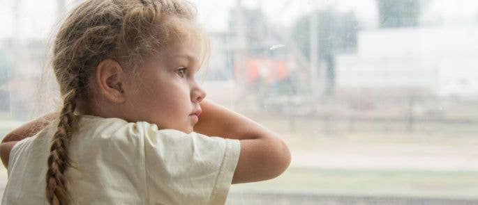 Young girl staring out of train window