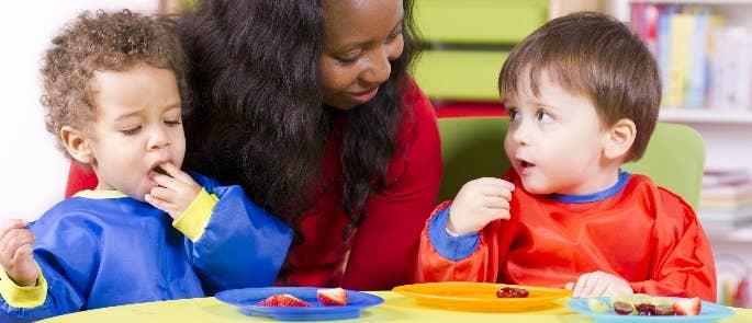 Female nursery teacher helping two children have fruit snacks.