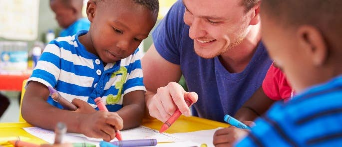 Male nursery teacher drawing with two children.