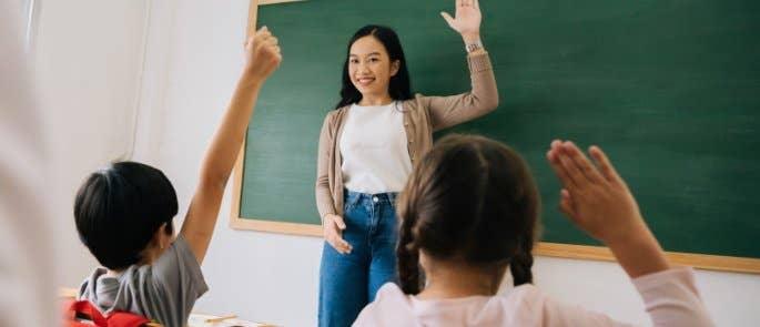Teacher encouraging pupils to raise hands