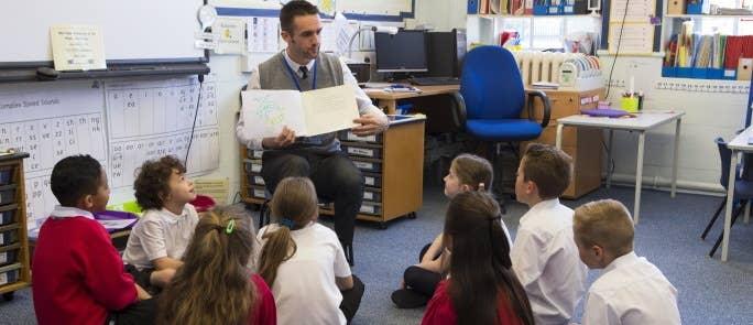 Male teacher explaining book to class of primary school children