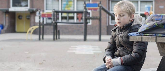 Young child sitting sadly on bench