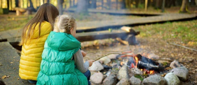 Two children cooking sausages on sticks around a campfire