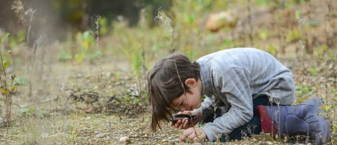 Child examining ground with magnifying glass