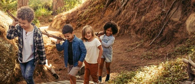 Children working together to carry log along forest path