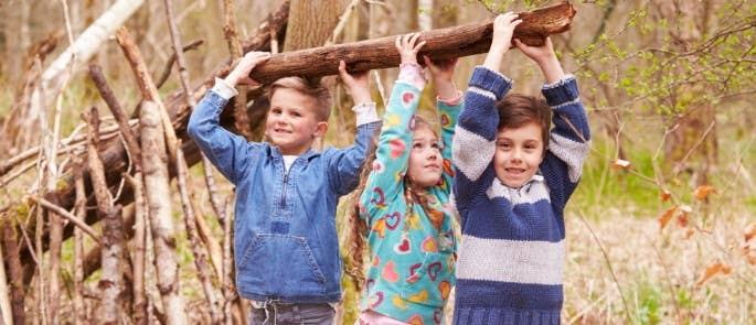 Children working together to make a shelter with big log