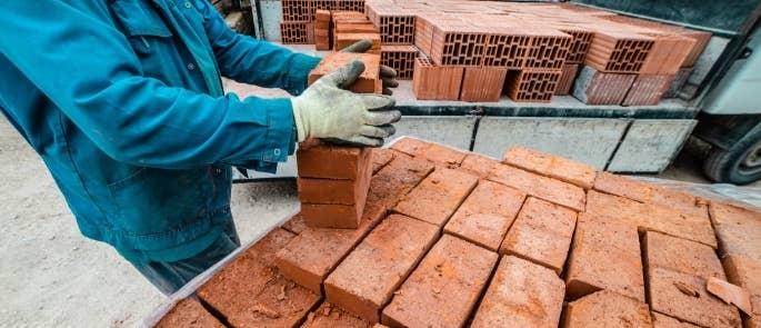Construction worker handling bricks delivery