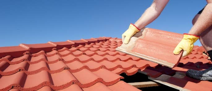 Worker on a roof laying tiles