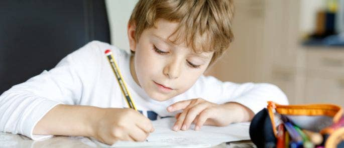 Young boy completing schoolwork at home