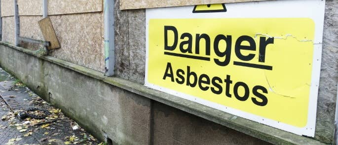 A sign at a building site saying 'Danger Asbestos'