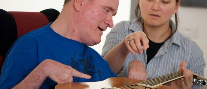 Gentleman with disability playing guitar in music therapy session