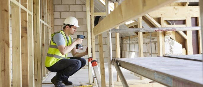 Male construction worker using a drill in a partly-constructed house