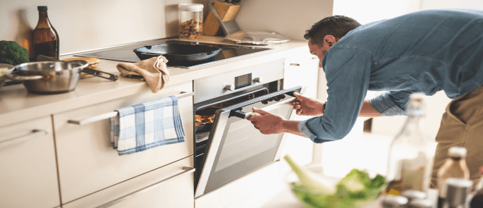 Man checking the temperature of his food in the oven