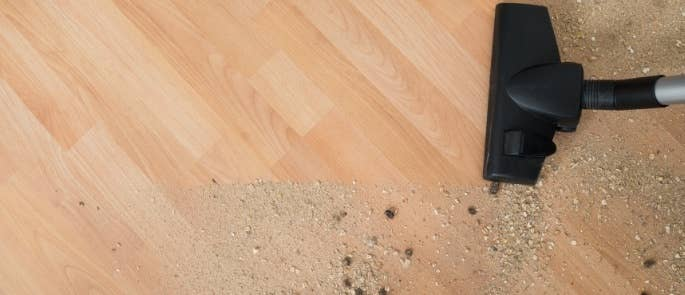 Cleaner hoovering dirt from floor