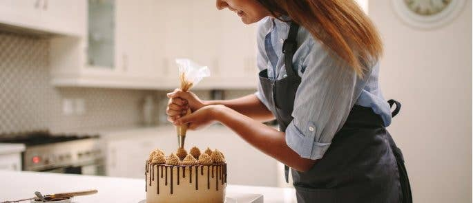 Woman decorating a cake for her food business