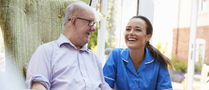 Carer and resident communicating in a care home