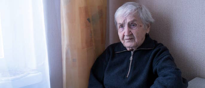 Elderly woman sat in her house worried about financial abuse