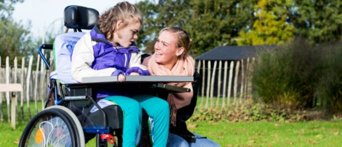 Young girl and carer communicating in the garden