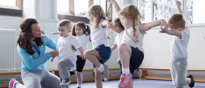 Teacher supporting students during a PE lesson
