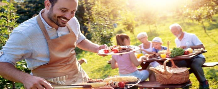 Man serving BBQ to his family