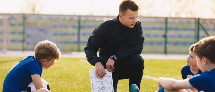 a man coaching children to play football