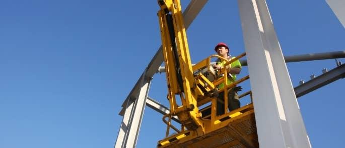 Construction worker using cherry picker