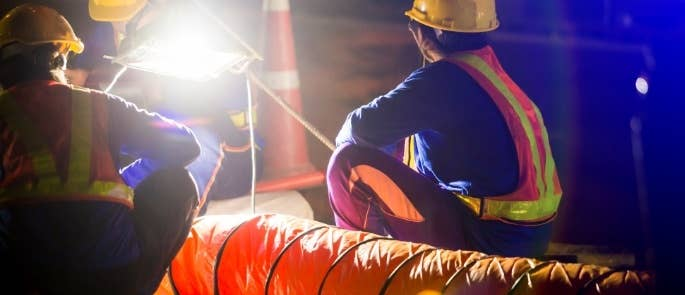 Construction workers with spotlight on site