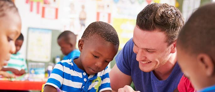 Teacher helping a child with their writing