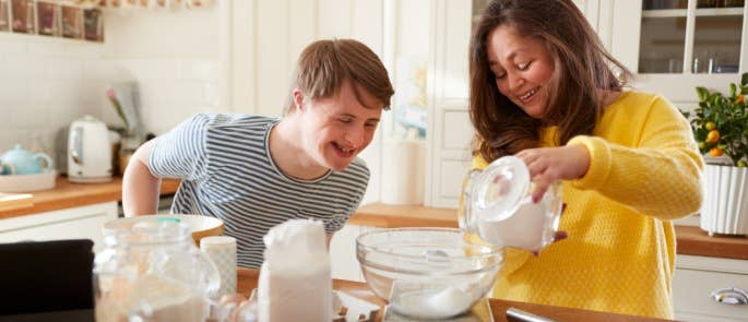 Support worker and service user baking together