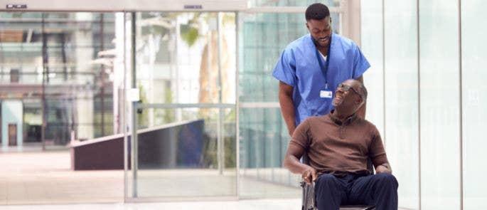 Nurse pushing patient in a wheelchair through hospital lobby
